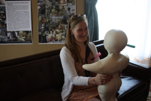 My friend Andrea interacts with the Telenoid, which imitated actions performed by a woman at a computer in the corner of the room.