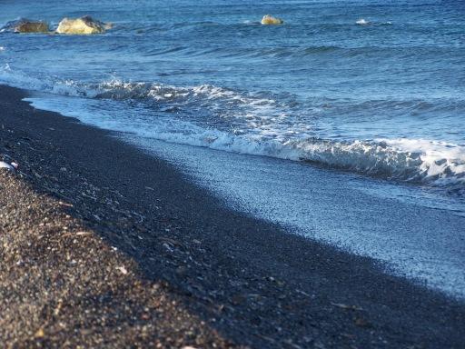 Brilliant blue waves crash into the black sand beach. May 2006.