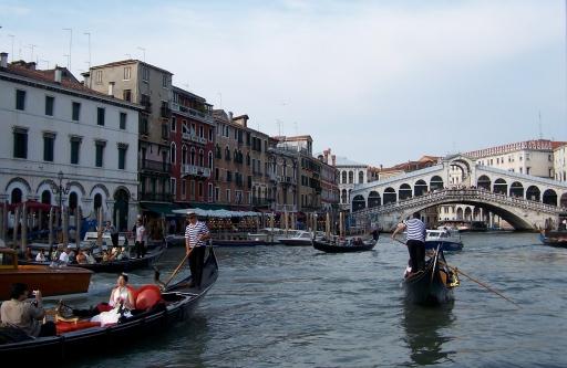Gondolas full of camera-toting tourists navigate Venice's Grand Canal near the Rialto Bridge.