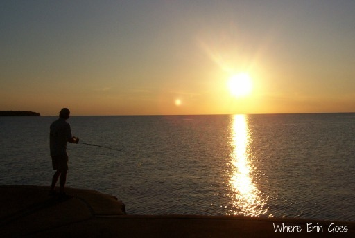 An angler fishes from the breakwall in Port Austin, Mich.