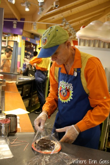 A cast member makes a custom treat at Goofy's Candy Co.